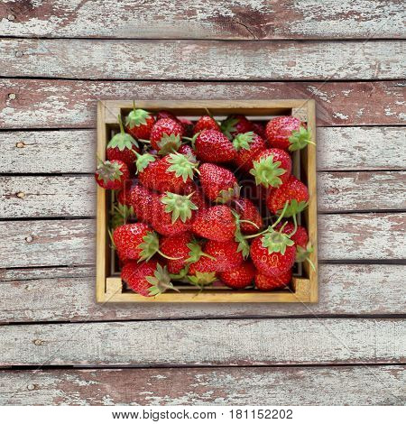 Strawberries in a wooden box. Top view. Ripe strawberries on a wooden background. Sweet and juicy berry with copy space for text. Top view.