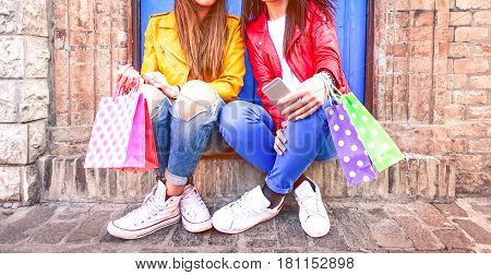 Trendy young women holding shoppers sitting on rustic wall background - Hipsters girls on colorful clothing and white sneakers legs and body cropped image - Casual chic fashion and leisure concept
