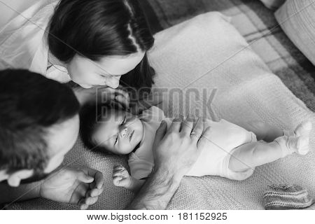 Parents with Newborn Baby Boy. Young parents look at a sleeping baby. View from above. Father's hand caressing a child. Black and white photo.