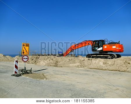 Orange Excavator On Pile Of Sand With Road Signs On Construction Site