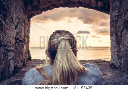Thoughtful woman devoted into contemplation of beautiful sunset over sea through window of old castle with dramatic sky and perspective view. View from behind. Concept for forecasting and way forward