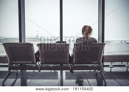 Pensive lonely woman tourist in airport terminal sitting on chair and looking on airplanes through window in departure holding zone