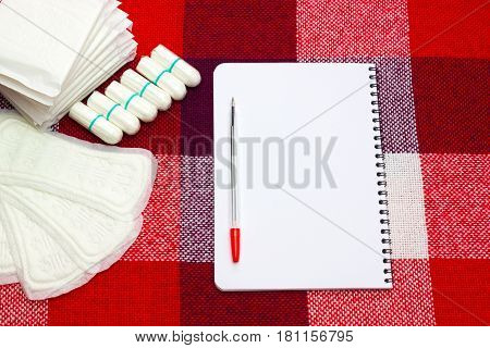 Notepad red pen for notes and woman hygiene protection menstruation sanitary pads and cotton tampon on the plaid at home. Protection for woman critical days gynecological menstruation cycle