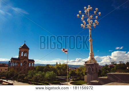 Photo of the Territory of Tbilisi Holy Trinity Cathedral Tsminda Sameba. Campanile, street lamp and georgian flag. Copy space. Blue sky. Green park. Travel concept. Faith
