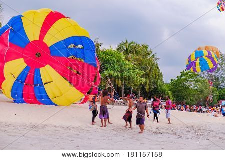 Langkawi, Malaysia - February 13, 2016: A group of Malaysian people engaged in parachuting extreme sports on Pantai Tengah Beach, Langkawi island, Malaysia. Summer vacation and fun.