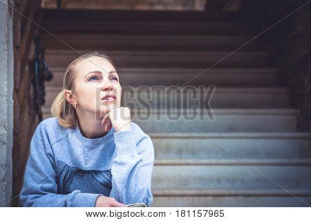 Thinking young woman sitting on stairs and look up with copy space. Concept for forecasting and way forward