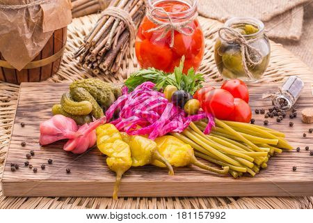 Marinated cherry tomatoes in a glass jar and pickles in a glass small jar