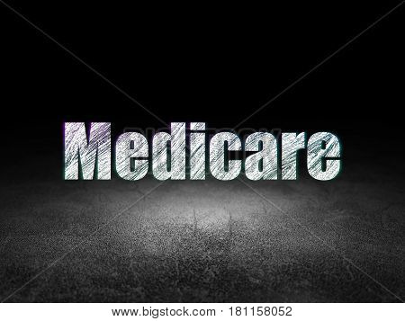 Health concept: Glowing text Medicare in grunge dark room with Dirty Floor, black background