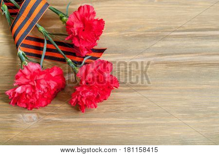 9 May background - red carnations and George ribbon as symbol of 9 May on the wooden background with free space for 9 May text. Concept of 9 May Victory day