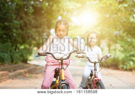 Portrait of active Asian family at nature park. Children biking outdoors. Morning sun flare background.