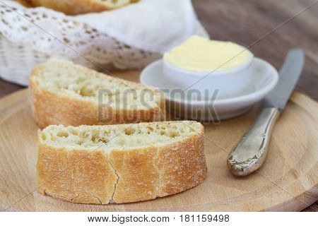 Italian ciabatta and butter on wooden board, closeup