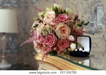 Wedding bouquet from pink roses and rings