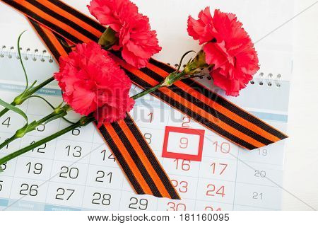 9 May - three red carnations and George on the calendar with framed 9 May date. Concept of 9 may Victory Day
