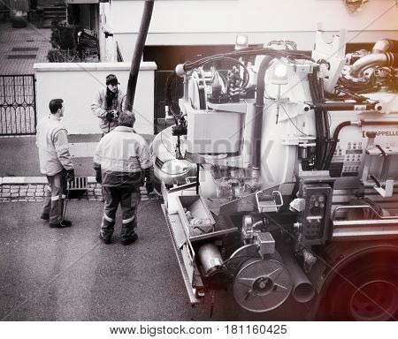 PARIS FRANCE - DEB 10 2017: Black and white of workers using sewerage truck and large pipe working on the clogged street rain water drain repairing and maintenance