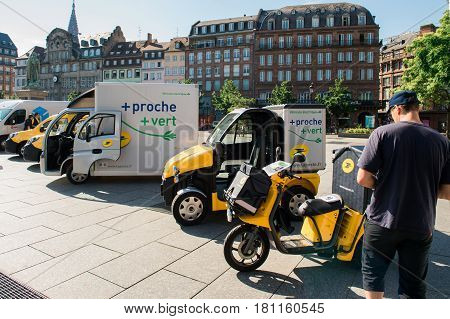STRASBOURG FRANCE - JUN 24 2016: Demonstration of postal fleet delivery electric cars and vans in a row in central Square Place Kleber early in the morning. La Poste is France's leading employer with a total workforce of 300000 working in postal shipping