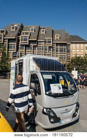 STRASBOURG FRANCE - JUN 24 2016: Man admiring Groupe Univers VE electric vehicle COLIBUS for postal distribution of parcels and letter in France by national postal carrier LA POSTE