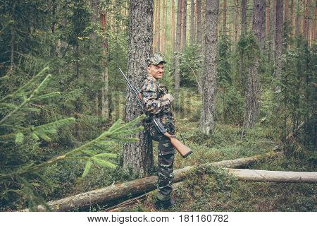 Hunter having rest in forest during hunting season
