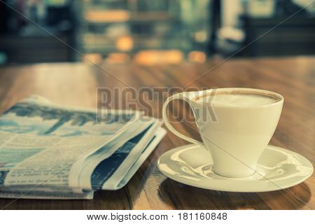 Cup of cappuccino with newspaper on the table in the morning coffee shop background warm tone