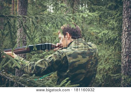 Hunter in forest during hunting season aiming before shoot