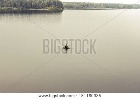 Only man in boat in the middle of vast expanses of tranquil lake. Symbolizing loneliness and searching