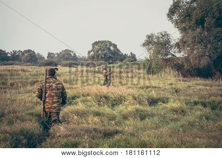 Hunters crossing through tall grass in rural field during hunting season