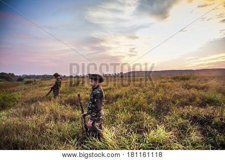 Hunters choosing good position for duck hunting in rural field during beautiful sunrise