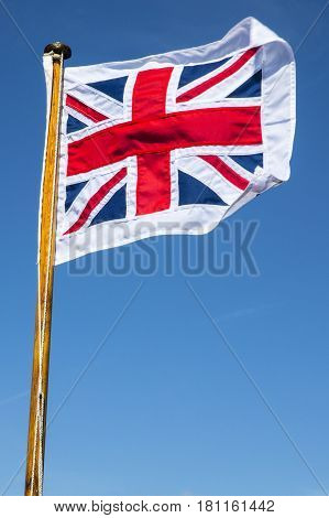 A shot of the Union Flag or Union Jack flying over a clear blue sky. With the surrounding white border the flag is called the Pilot Jack and is used on a boat when it is in harbour.