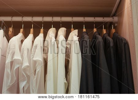 White and black shirts on trempele in the closet.