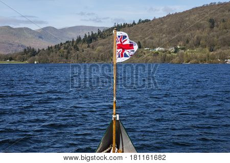 The Pilot Jack (Union Flag with surrounding white border) flying on a boat traveling on Lake Windermere in the Lake District UK.