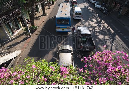 Traffic view from bridge above small road in Bangkok with cars moving, Thailand, outdoor city landscape