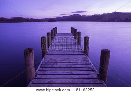 An evening view of a jetty on Coniston Water in the Lake District in Cumbria UK.