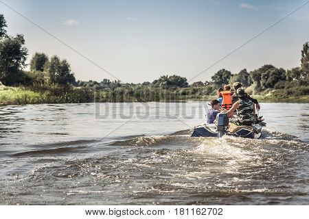 Group of people sailing on motor boat by river in summer day to the hunting camp during hunting season