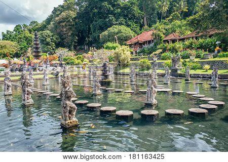 Water Palace of Tirta Gangga - famous landmark of Bali island, Karangasem, Indonesia. Popular beautiful water palace with fountains and traditional hindu demons statues, travel landscape photography