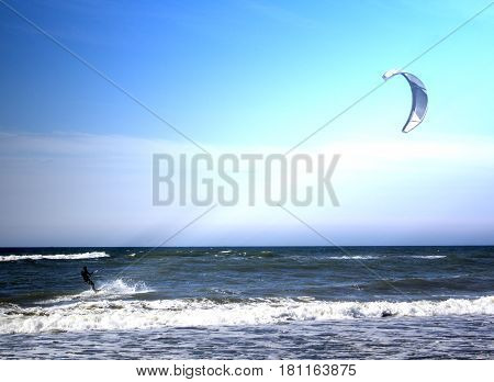 Kitesurfer jumping on a beautiful background of spray during the sunset.
