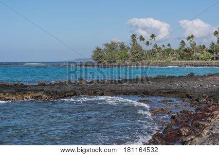 Curvy Coastline: Poipu Coastline, with cloudy blue sky, and palms, on Kauai