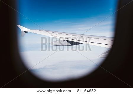 View through the airplane window on wing and blue sky