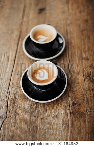 Two cups with coffee on wooden background
