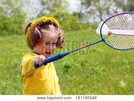 little girl playing badminton on spring meadow