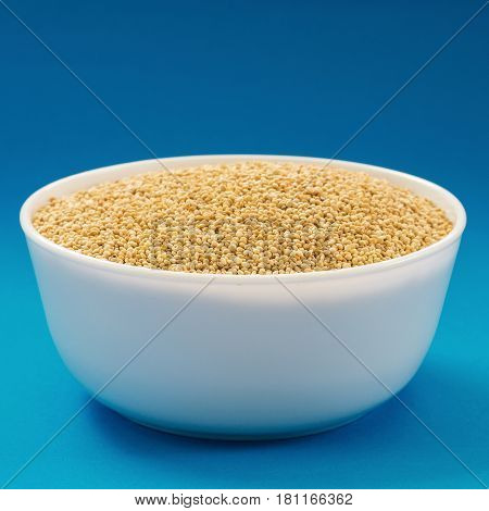 Raw white quinoa in a bowl on blue background. Vegan source of protein.