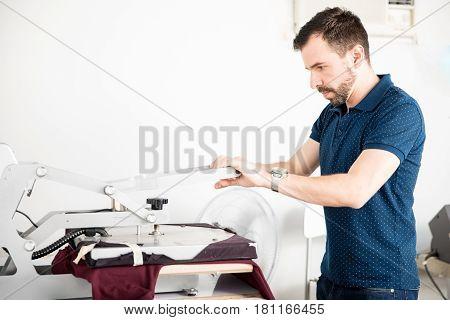 Man Printing Shirt In A Workshop