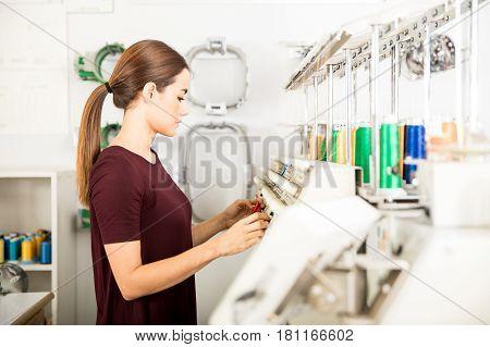 Woman Setting Up Embroidery Machine