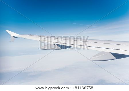 Airplane wing with the blue sky in the background