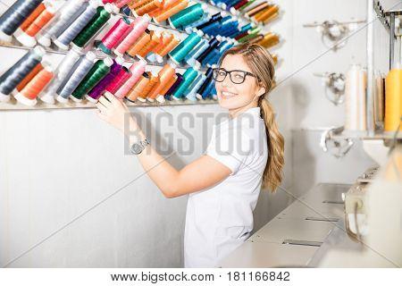 Cute Woman Looking At Thread Rolls