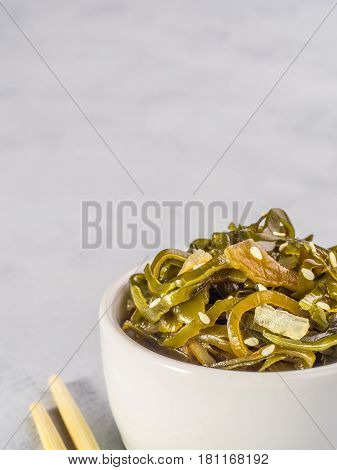 Close up view of kelp seaweed salad with sesame seeds on gray concrete background. Copy space. Vertical.