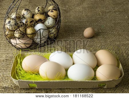 a lot of chicken eggs and quail eggs beige and white lies of a metal structure in the shape of a heart and an ear lying on the wooden table covered with burlap