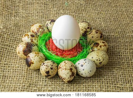 quail eggs and chicken egg with  are in a circle around the plastic blue bowl of red salt on a wooden table with natural burlap