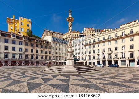 Town Hall Square with a beautiful geometric mosaic in Lisbon, Portugal. In the center of the square the pillory The Pelourinho de Lisboa