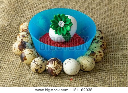 quail eggs and chicken egg with green bow are in a circle around the plastic blue bowl of red salt on a wooden table with natural burlap