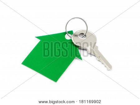 A house made of green cardboard and a key on a white background