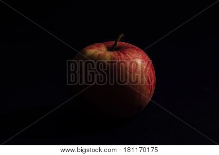 Red apple in the shade on a black background. Isolated.
